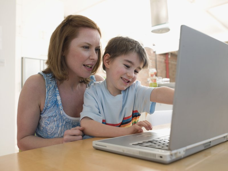 Home-schooling mum and son learning tech together on their laptop