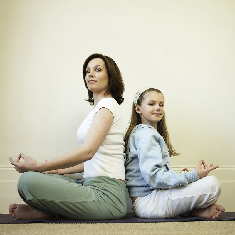 Home-schooling mum and daughter sitting back-to-back in yoga pose