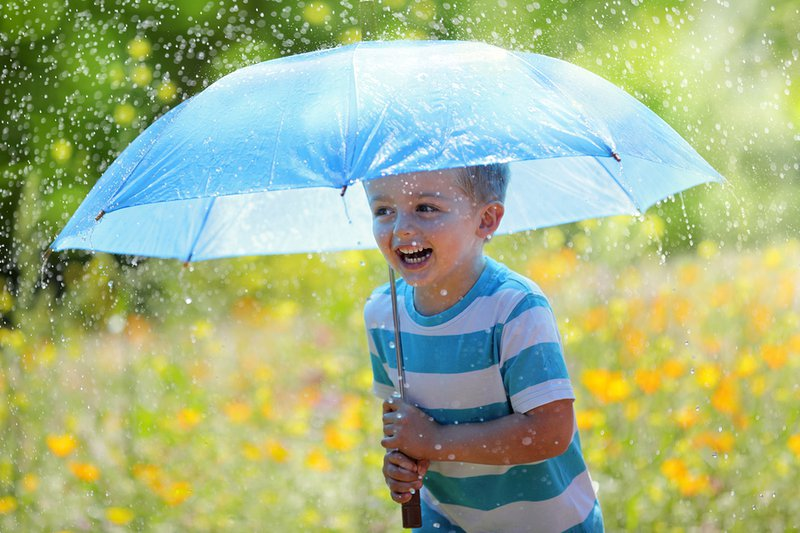 Rainy day pta fair ideas from PTAsocial - Little boy laughing in the rain with an umbrella