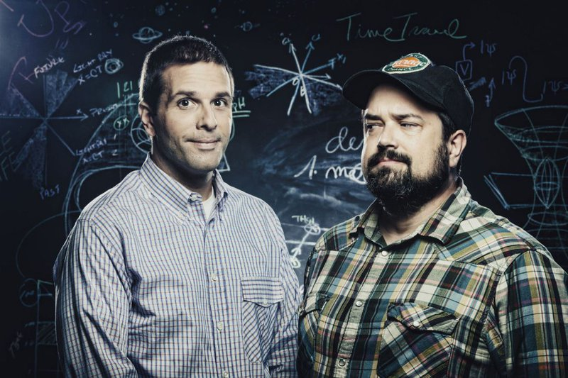 picture of Josh and Chuck from Stuff You Should Know, standing in front of a blackboard with scientific mumbo jumbo written on it