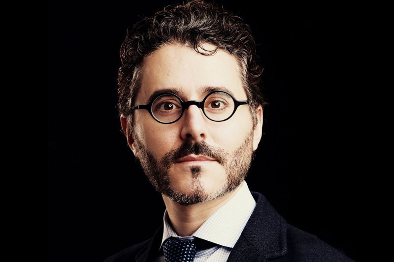 Picture of Michael Barbaro against a black background. he has h-curly hair, a grey and black beard, and round glasses