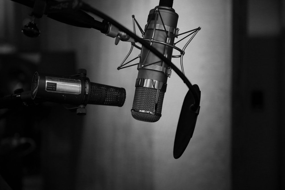 grayscale photography of condenser microphone with pop filter to record a podcast