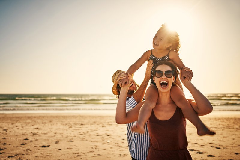 Shot of an adorable little girl spending the day at the beach with her parents