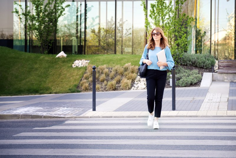 Full length shot of middle aged businesswoman holding laptop in her hand while walking on pedestrian crossing.
