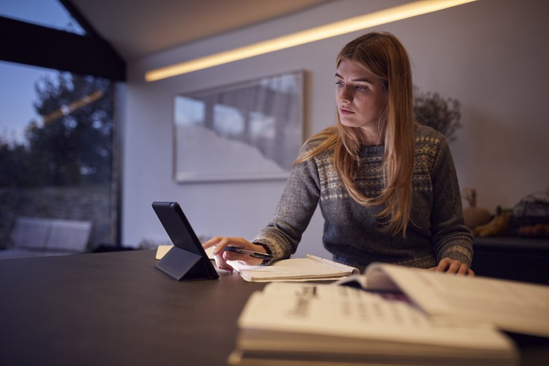 Evening Shot Of Woman In Kitchen Working Or Studying From Home Using Digital Tablet