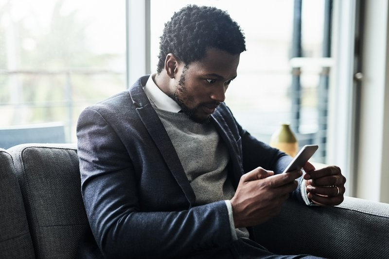 Shot of a young businessman looking at his cellphone in shock while sitting on a couch in an office