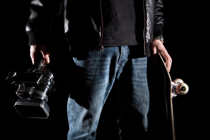 Skateboarder Holding a video camera and a skateboard isolated on black background