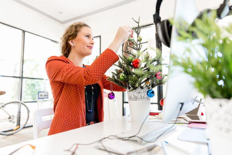 Femme décore sapin de Noël au bureau pendant les vacances de Noël