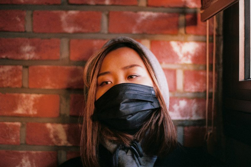 young Asian woman sitting down with a hoodie and a black surgical mask