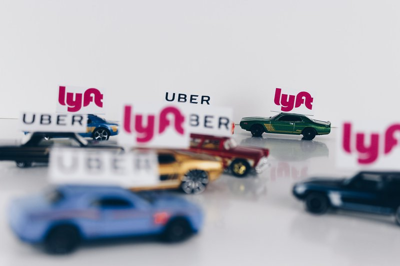 The ride-sharing wars! Uber and Lyft conceptual road concept using toy cars.