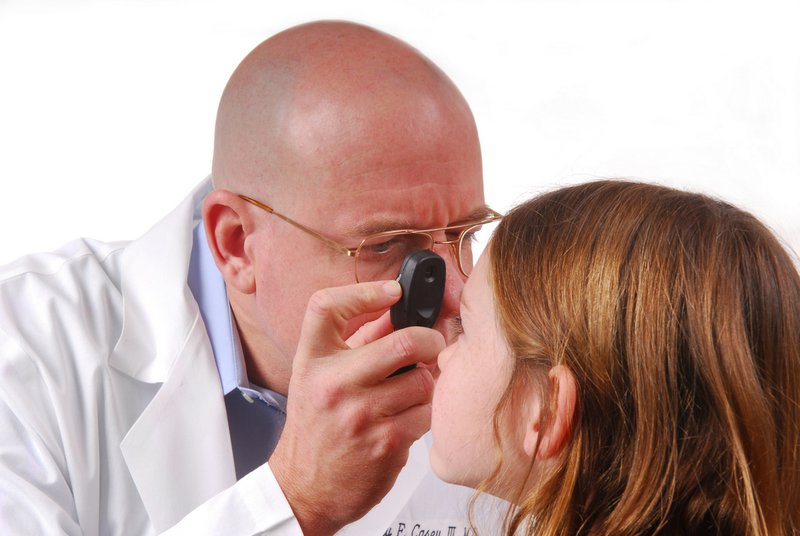 ophthalmology marketing doctor performs eye exam of female child