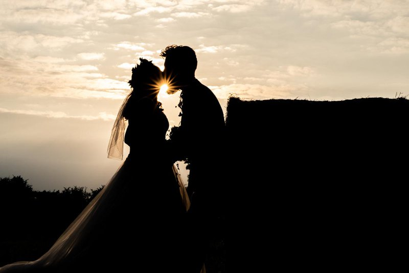 candid wedding photography - artistic shot of the bride and groom at sunset