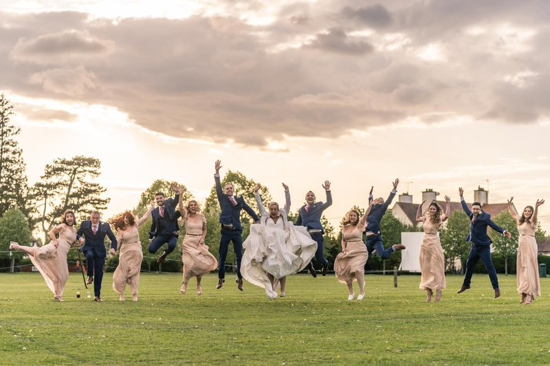 group wedding photos - fun group shot of wedding party jumping in the air