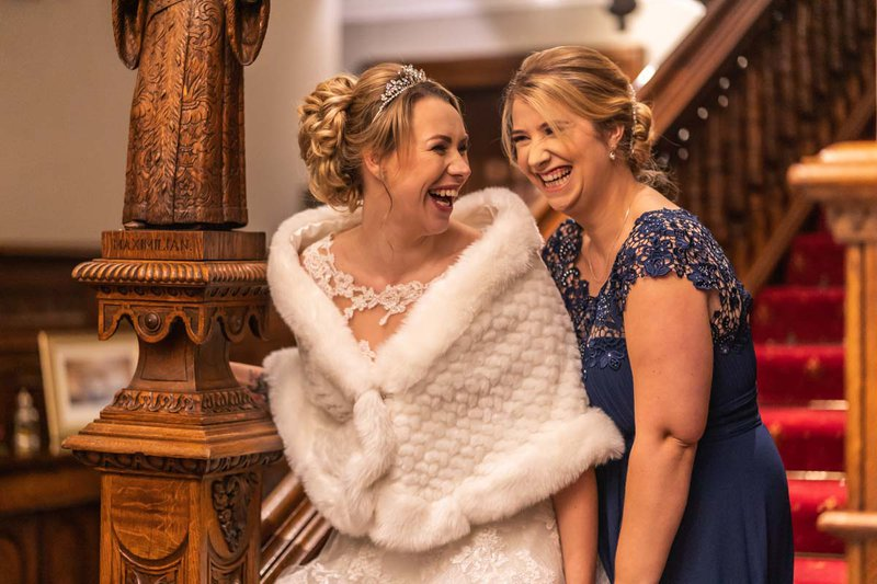 wedding photos - a bride and her bridesmaid laugh together