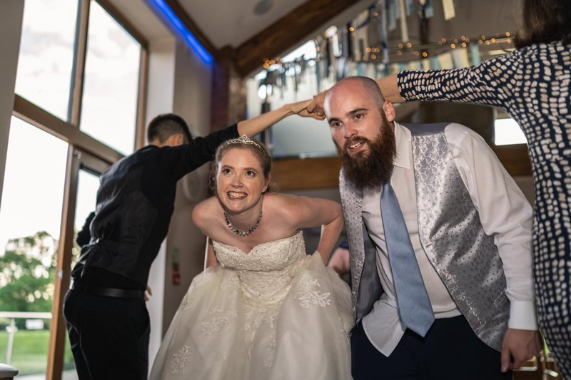 candid wedding photography - bride and groom walking under arms of guests