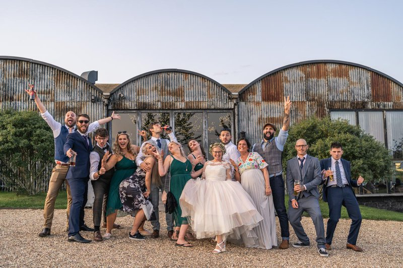 group wedding photos - fun group shot in front of converted barn